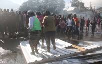 Tired of delays in redevelopment, angry Imizamo Yethu residents blocked roads using iron sheeting and rocks. Picture: Bertram Malgas/EWN