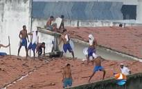 This grab from TV Ponta Negra taken on 14 January 2017 of the Alcacuz Penitentiary Center near Natal, Rio Grande do Norte state, northeastern Brazil shows inmates throwing objects from the prison roof during a riot. Picture: AFP