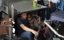 People wait at the Fort Lauderdale-Hollywood International airport after a shooting took place near the baggage claim on 6 January, 2017 in Fort Lauderdale, Florida. Picture: AFP.