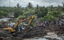 Residents stand next to an excavator working at the site of a dump collapse in a poor district of Maputo on 19 February 2018. Picture: AFP