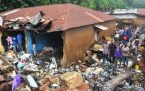 People stand near a damaged house after a rubbish dump collapsed the day before following heavy rain on the outskirts of Conakry. Picture: AFP.