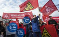 Employees of EvoBus, a subsidiary company of Daimler AG, participate in a warning strike called by the country's largest union, the IG-Metall, in Mannheim, southwestern Germany, on 11 January 2018. Picture: AFP.