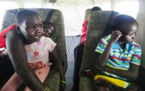 This handout picture taken and released by Unicef on 11 June 2016 shows Nyabitu Saleh (L), 7 years old, next to her brother Mubarak (R), crying of fear while landing to Kodok, South Sudan, in a UN plane. Picture: Unicef/AFP.