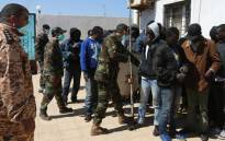 FILE: African migrants wait at a Libyan Naval forces post in Tripoli on 10 April 2014 after their boat was intercepted en route to Europe and brought back to Libya. Picture: AFP.