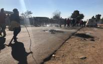 Police monitoring a protest in Primrose on the East Rand where residents of the Makause Informal Settlement have barricaded the main roads with burning tyres on 22 May 2017. Picture: Kgothatso Mogale/EWN.