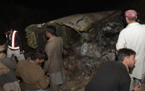 Pakistani residents stand beside the wreckage of the crashed PIA passenger plane Flight PK661 at the site in the village of Saddha Batolni in the Abbottabad district of Khyber Pakhtunkhwa province on 7 December, 2016. Picture: AFP.