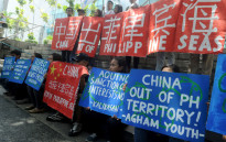 Filipino environmental activists display placards during a rally outside China's consular office in Manila on 11 May 2015, against China's reclamation and construction activities on islands and reefs in the Spratly Group of the South China Sea that are also claimed by the Philippines. Picture: AFP/Jay Directo.