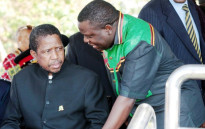Edgar Lungu (l) talks to foreign affairs minister Harry Kalaba during a military exhibition march past on 24 October, 2014 to mark Zambia's 50th Independence celebration. Picture: AFP.