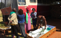 Outside the bus in which Betty Ketani was left to die, her family called out to her spirit. Picture: Alex Eliseev/EWN.