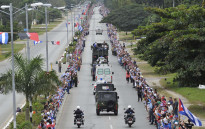 People line the road to see the convoy carrying the urn with the ashes of Cuban leader Fidel Castro as it drives through Sancti Spiritus, Cuba, on 1 December, 2016 during its four-day journey across the island for the burial in Santiago de Cuba. Picture: AFP.