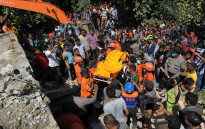 Indonesian search and rescue personnel retrieve a body from the rubble of a collapsed building following an earthquake in Pidie, Aceh province on 7 December, 2016. Picture: AFP.
