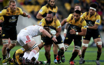 Loni Uhila (C) of the Hurricanes is tackled by Sam Cane (C bottom) of the Chiefs during the Super Rugby semi-finals match between the Wellington Hurricanes and Waikato Chiefs at Westpac Stadium in Wellington on July 30, 2016. Picture: AFP