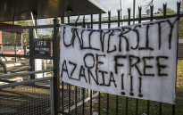 Protesting students at the University of the Free State placed a banner on a gate close to the entrance of the institution's main campus on 25 February 2016. Picture: Reinart Toerien/EWN.