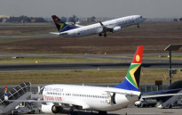 A South African airways flight takes off as another one is parked in a bay on the tarmac Johannesburg O.R Tambo International airport in Johannesburg, South Africa. Picture: AFP
