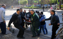 Egyptian emergency services carry a wounded victim at the site of a bomb attack next to a police checkpoint in the western Talibiya district of the capital Cairo on December 9, 2016. Picture: AFP
