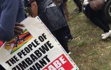A protester carries a placard calling for President Robert Mugabe to relinquish power during a protest march in Harare on 18 November 2017. Picture: EWN