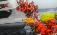 Screengrab of crew members and passengers rescued from a sinking Robin Island ferry, two passengers were treated at a local hospital.