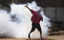 FILE: A supporter of Zimbabwe's MDC throws back a tear gas canister as protesters clash with police during a march against police brutality on August 24, 2016 in Harare, Zimbabwe. Picture: AFP