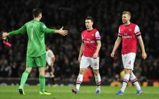 Arsenal's goalkeeper Wojciech Szczesny celebrates at the end of the match with Laurent Koscielny and Per Mertesacker after winning their match against Liverpool at the Emirates Stadium in north London, on 2 November, 2013. Picture:AFP
