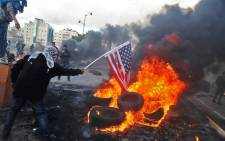 A Palestinian protester sets alight an America flag during clashes with Israeli troops at a protest against US President Donald Trump's decision to recognize Jerusalem as the capital of Israel, near the Jewish settlement of Beit El, near the West Bank city of Ramallah on 7 December 2017. Picture: AFP.