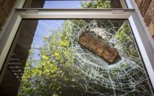 A brick remains lodged in a window. Picture: EWN