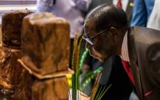 Zimbabwe's President Robert Mugabe blows out candles during a private ceremony to celebrate his 93rd birthday on 21 February, 2017 in Harare. Picture: AFP.