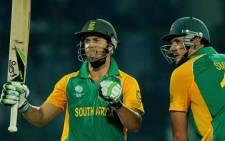 AB de Villiers celebrates after scoring his half-century as captain Graeme Smith looks on February 24, 2011