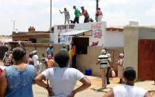 A group of looters are breaking into a foreign-owned store in White City, Soweto on 22 January 2014. Picture: Gia Nicolaides/EWN
