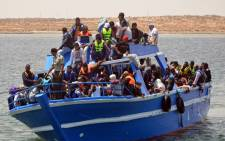 FILE: Migrants arrive at the port in the Tunisian town of Ben Guerdane, some 40 km west of the Libyan border, following their rescue by Tunisias coastguard and navy after their vessel overturned off Libya, on 10 June 2015. Picture: AFP.