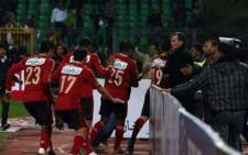 Egyptian Al-Ahly players escape from the field as fans of Al-Masry team rush to the pit during clashes that erupted after a football match between the two teams in Port Said. Picture: AFP