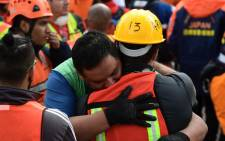 Rescue workers embrace each other after a seismic alert sounded in Mexico City on 23 September 2017, four days after the powerful quake that hit central Mexico. Picture: AFP.