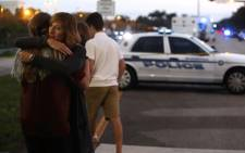 Kristi Gilroy hugs a young woman at a police check point near the Marjory Stoneman Douglas High School where 17 people yesterday were killed by a gunman on 15 February 2018 in Parkland, Florida. Picture: AFP.