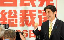 New Liberal Democratic Party (LDP) president Shinzo Abe (C) poses for photographers prior to his news conference after the party's presidential election at their headquarters in Tokyo on September 26, 2012. Picture: AFP PHOTO / KAZUHIRO