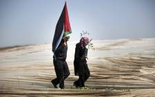 """A man holding a Palestinian flag and a woman carrying an olive tree, walk through rows of greenhouses on """"Land Day"""" during which people notably plant olive trees on 29 March, 2014 near the Israeli border in Jabalia, in the northern Gaza Strip. Picture: AFP."""
