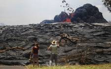 Kate Lilly (L) and Will Divine look on as lava erupts from a Kilauea volcano fissure in Leilani Estates, on Hawaii's Big Island, on 24 May, 2018 in Pahoa, Hawaii. Picture: AFP
