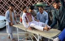 FILE: Afghan volunteers carry an injured man on a stretcher to a hospital after a suicide bomber blew himself in Jalalabad on 16 June 2018. Picture: AFP.
