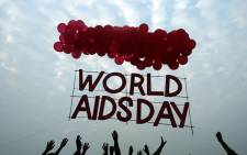 FILE: Indian social activists and children release a World AIDS Day awareness sign tied with ballons in Kolkata on 1 December, 2015. Picture: AFP.