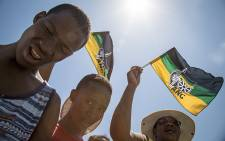 A boy prays while other ANC supporters wave flags at the ANC 104 birthday rally in Grabouw. Picture: Thomas Holder/EWN