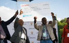 President Jacob Zuma hands over a cheque to the leader of the Mahishi community as part of the first phase of compensation in the land claim agreement.  Picture: Christa Eybers/EWN.