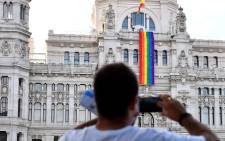 A man takes pictures of a giant rainbow banner displayed on the facade of the Cibeles Palace, the Madrid City Hall, during an official ceremony in Madrid on June 26, 2017. Picture: AFP