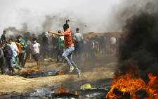 A Palestinian demonstrator uses a slingshot to throw stones during clashes with Israeli security forces following a protest on the Israel-Gaza border east of the Jabalia refugee camp in the northern Gaza Strip on 6 April 2018. Picture: AFP