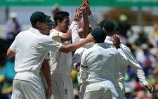 Australia's Mitchell Starc (3rd L) celebrates with teammates after taking a wicket. Picture: AFP