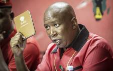 EFF leader Julius Malema holds up a copy of South Africa's constitution while addressing the media following the Constitutional Court's ruling that President Jacob Zuma must pay back some of the money spent on upgrades to his Nkandla homestead. Picture: Reinart Toerien/EWN.