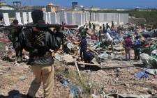 FILE: Civilians and soldiers stand among scattered objects and belongings at the scene of a car bomb attack near the Peace Hotel of the capital Mogadishu on 2 January 2017. Picture: AFP.