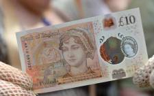 People in period costume pose with on the Bank of England's new ten pound notes, featuring author Jane Austen, during its launch at Winchester Cathedral in Winchester, southern England, on 18 July 2017. Picture: AFP.