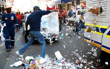 A protester empties a refuse bag into a road during the municipal workers protest in the Joburg CBD on 27 July, 2009. Picture: Taurai Maduna/Eyewitness News