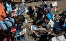 FILE: People read newspapers in Kisumu, Kenya on 28 October 2017 following a re-run of elections. Picture: AFP