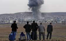 FILE: Residents watch smoke from an explosion rising over the Syrian city of Kobani as they watch the apparent US-led coalition's airstrike against IS positions in the border region. Picture: EPA.