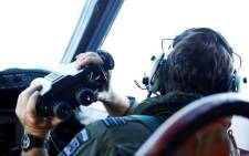 FILE: Wing Commander Rob Shearer looks through binoculars on the flight deck of a Royal New Zealand Air Force P-3K2 Orion aircraft searching for missing Malaysian Airlines flight MH370. Picture: AFP.