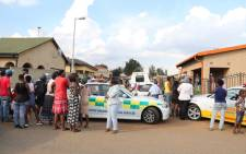 Community members look on as police negotiate with a Soweto man who has is holding his partner hostage at her home in Tladi. Picture: Christa Eybers/EWN.